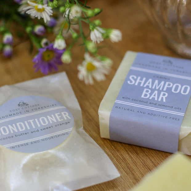 solid conditioner bar and natural shampoo bar in plastic free wrapping on a wooden table