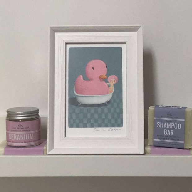 cooperillo framed picture of rubber duck next to a shampoo bar on a shelf