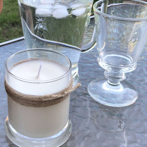 large lemongrass candle on an outside table in summer