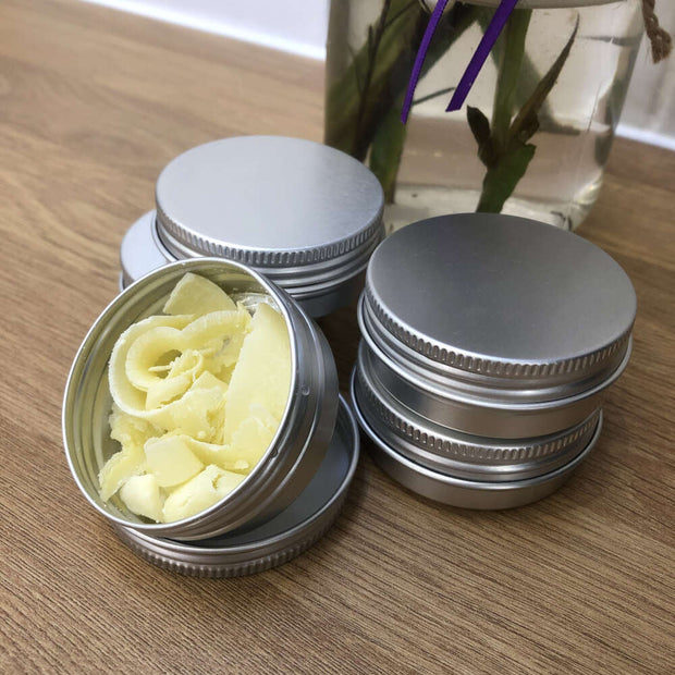 handmade soap shavings in an aluminium tin with 4 more tins stacked behind