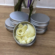 natural soap shavings in an aluminium tin with 4 more tins stacked behind