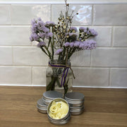 natural soap shavings in an aluminium tin with 4 more tins stacked behind along side a vase of purple flowers
