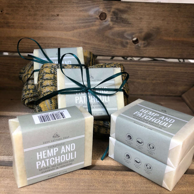 handmade hemp and patchouli soap bars stacked with soap and sock bundles in wooden crate