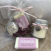 geranium travel soap and soy wax candle in front of bundle of soap and lip balm in biodegradable packaging with a pink ribbon