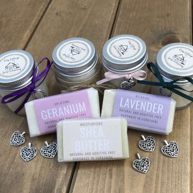 fragranced travel soaps and soy candles arranged on a wooden bench top