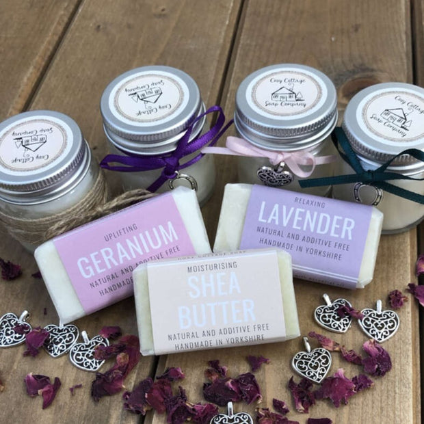 fragranced travel soaps and soy candles arranged on a wooden bench top with purple petals
