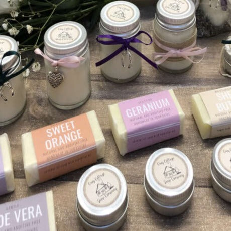travel soaps, candles and lip balms on a wooden bench top with with flowers