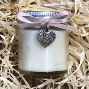 handmade soy wax candle with pink ribbon on a bed of straw