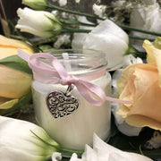 handmade soy wax candle with pink ribbon surrounded by roses