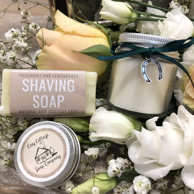 handmade shaving travel soap with soy wax candle and lip balm on a bed of flowers