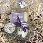 relaxing lavender travel soap, soy wax candle and lip balm bundle on a bed of straw