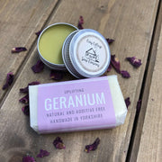 uplifting geranium travel soap bar and natural lip balm on a bed of purple petals