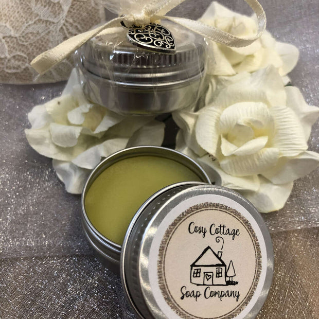 lip balm with lid off on a bed of white flower heads