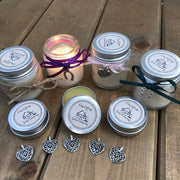 soy wax candles and natual lip balms lined up on a wooden work top with love hearts