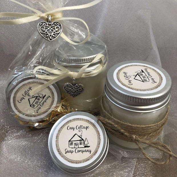 soy wax candle and natural lip balm in front of a bundle in biodegradable packaging with cream ribbon