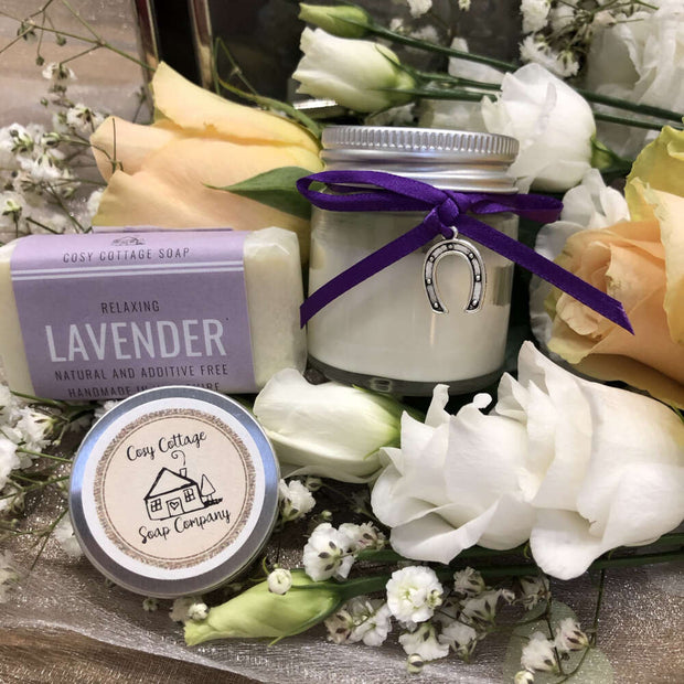 relaxing lavender travel soap, soy wax candle and lip balm bundle on a bed of flowers