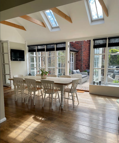 converted barn dining room area with high beam ceiling and home made dining table