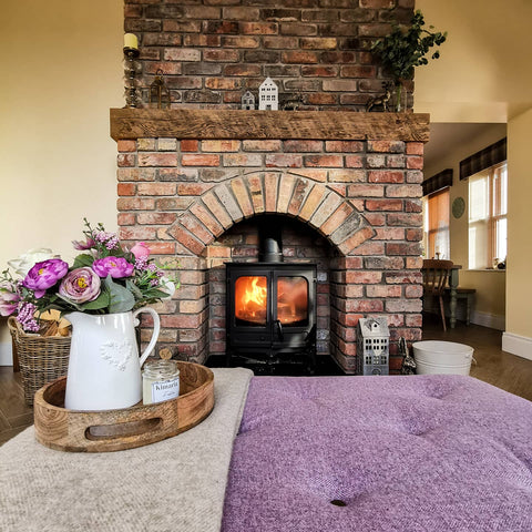 country cottage living room with log burner and footstool