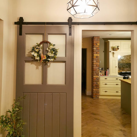 internal barn door opens into country cottage kitchen