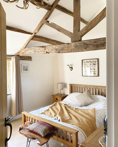beautiful cottage bedroom with wooden ceiling beams