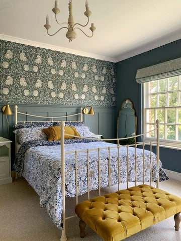 country bedroom with wallpaper feature wall and antique dressing table