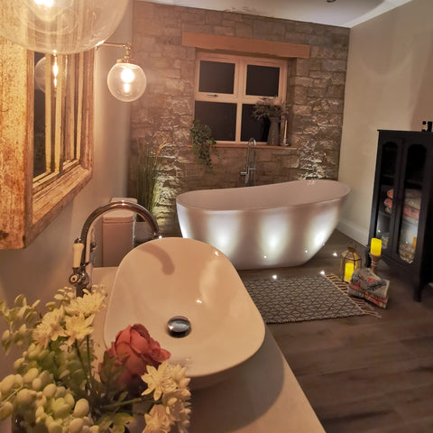 stunning bathroom with stone wall and freestanding roll-top bath