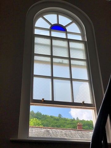 stained arched window on staircase