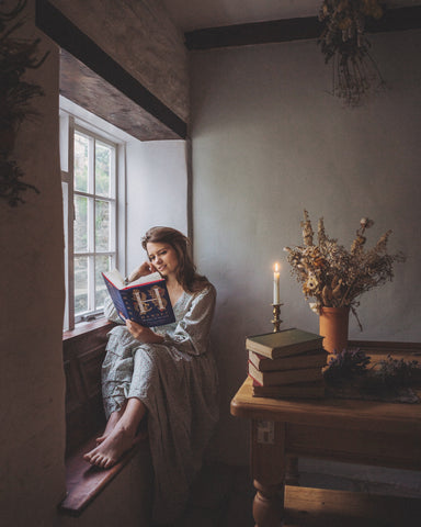 girl reading on a cosy window seat