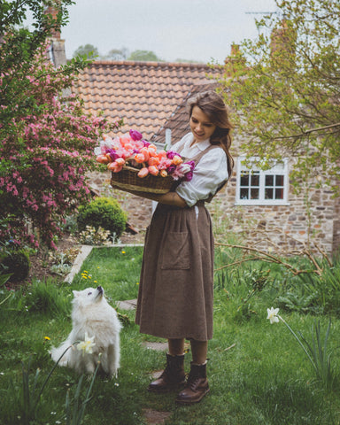 Mona carrying basket of flowers in garden with dog