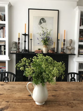 country dining table with plants candles and bookshelves