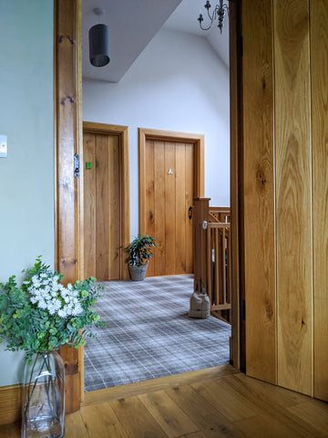 country theme upstairs landing with wooden latch doors and grey tartan carpet