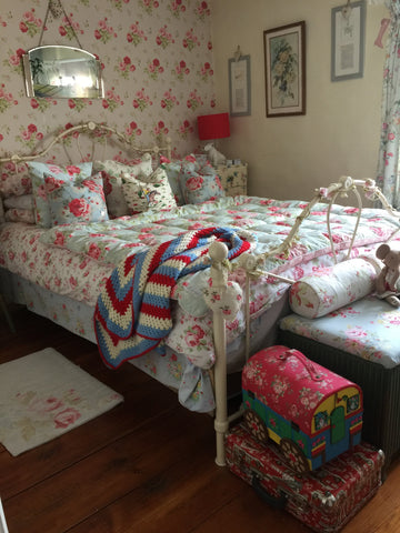 country bedroom with antique metal frame bed and floral theme decor