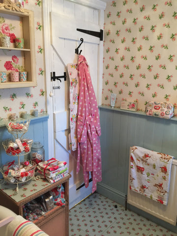 country bathroom with wainscoting and Cath Kidston wallpaper and floor tiles