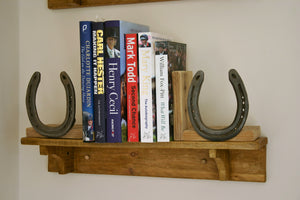 Image of Books On a Shelf With Wooden Bookends Decorated with Horseshoe