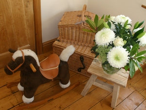 Rustic wooden stool  and rocking horse in children's country theme bedroom