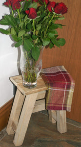 Natural wood traditional milking stool used as a side table with a vase of red roses on top