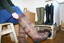 Load image into Gallery viewer, Image of person sitting on stool pulling on country boots with a boot display storage stand in the background
