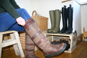 Image of person sitting on stool pulling on country boots with a boot display storage stand in the background