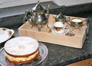 wooden serving tray with horseshoe handles with teapot and cake