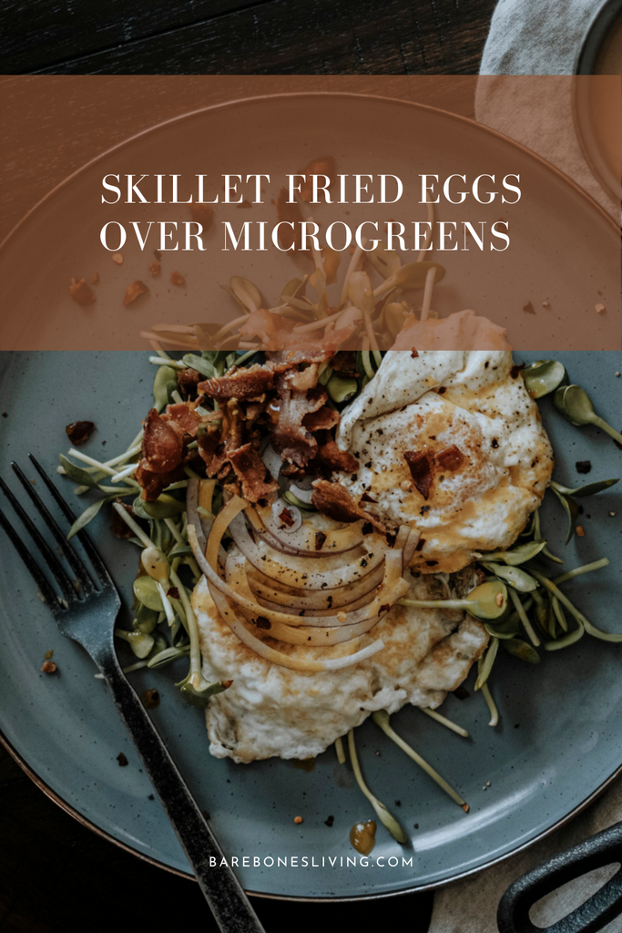 Skillet fried eggs over microgreens with bacon crumbles