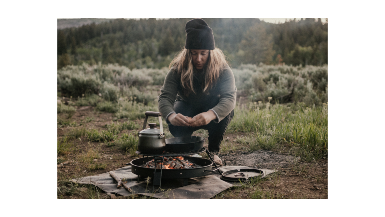 Women cooking breakfast in the wilderness over a fire pit