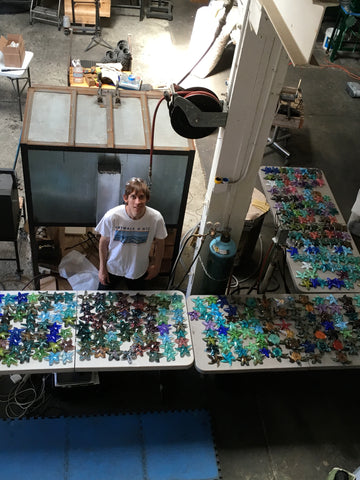 John Gibbons standing in his studio looking up surrounded by hundreds of colorful glass starfish on tables