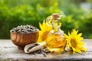 bottle of sunflower oil with vitamin e next to sunflowers and bowl of sunflower seeds