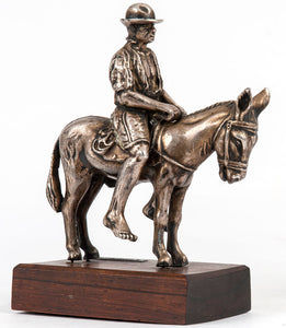 Silver figurine of an Afro-American man on a donkey