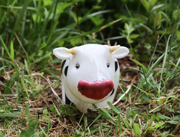 Handmade glass Holstein cow sitting in the grass.