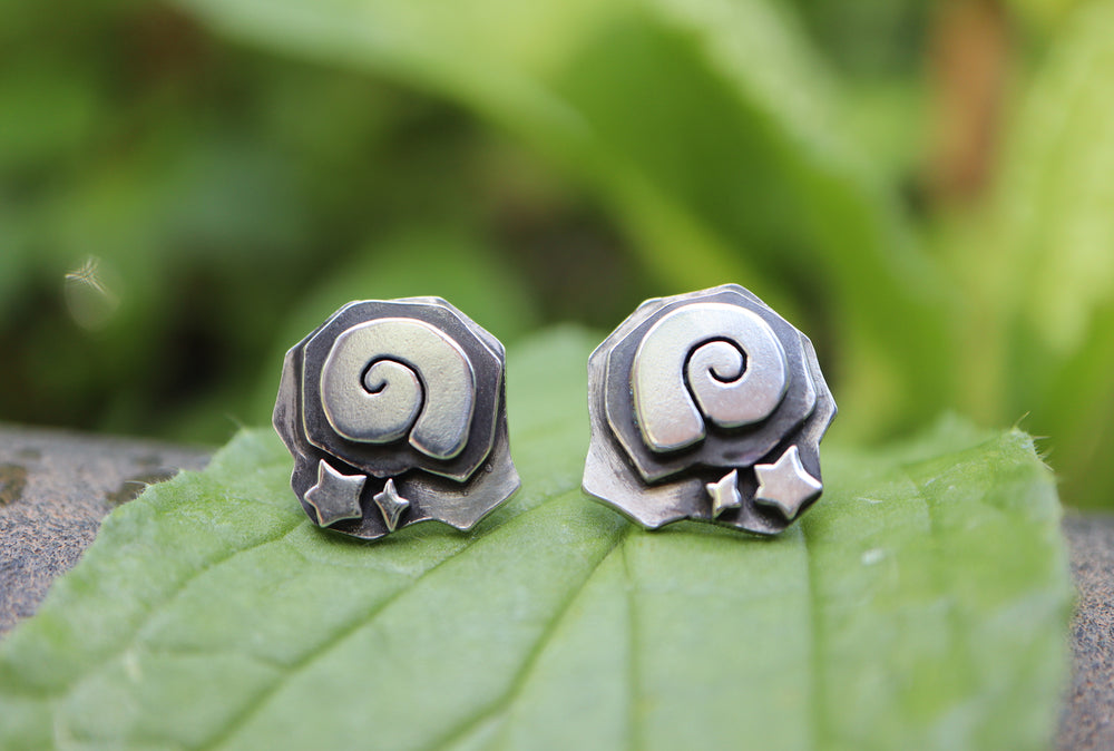 Sterling silver handmade Animal Crossing New Horizon fossil earrings are shown on a light green leaf.
