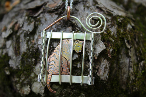 A caged tiger made from silver and copper and worn on a necklace
