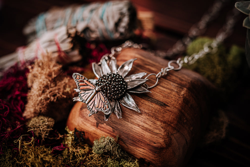 A handmade sterling silver and copper monarch butterfly on an echinacea flower and can be worn as a necklace. It is shown on a piece of week with mosses and greenery around it.