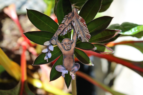 Handmade pendant of an orangutan baby holding onto a hand cut palm tree branch