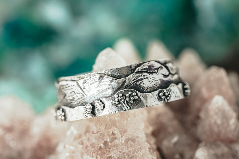 A close up of the New Hampshire White Mountains ring with tiny trees and bushes on the band.